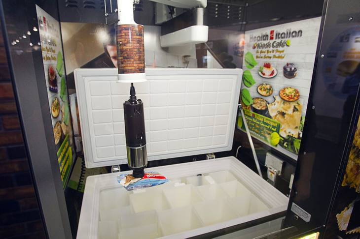 A mechanical vacuum arm picks an ice cream sandwich from a freezer box at the Fastcorp booth during the NAMA (National Automatic Merchandising Association) One Show at the Sands Expo Center Wednesday, April 25, 2013. The NAMA One Show convention serves the vending, coffee and food service industries.