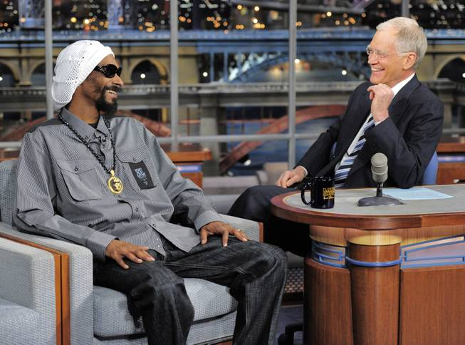 In this photo provided by CBS, rapper/actor Snoop Lion, formerly Snoop Dogg, left, talks with host David Letterman on the set of the Late Show with David Letterman, Thursday, April 25, 2103 in New York.