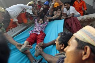Rescuers lower down a survivor from the debris of a building that collapsed in Savar, near Dhaka, Bangladesh, Wednesday, April 24, 2013. An eight-storey building housing several garment factories collapsed near Bangladeshs capital on Wednesday, killing dozens of people and trapping many more under a jumbled mess of concrete. Rescuers tried to cut through the debris with earthmovers, drilling machines and their bare hands.