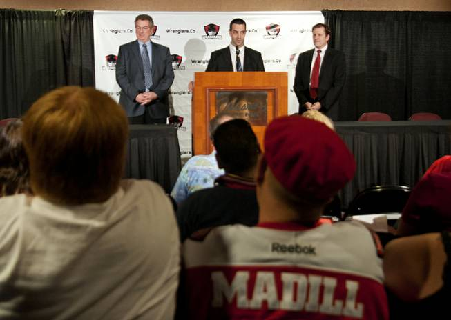 A fan wearing a Mike Madill jersey sits in the audience as Madill (center) fields questions with Wranglers team owner Gary Jacobs, left, and general manager Billy Johnson during a press conference announcing Madill being appointed head coach in April 2013.