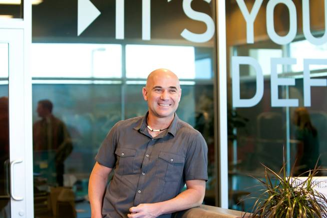 Tennis champion Andre Agassi chats with colleagues in the lobby while waiting for his trainer Gil Reyes to arrive to demonstrate their BILT training equipment, designed by Agassi and Reyes, at the BILT Headquarters in Las Vegas Friday, April 26, 2013.