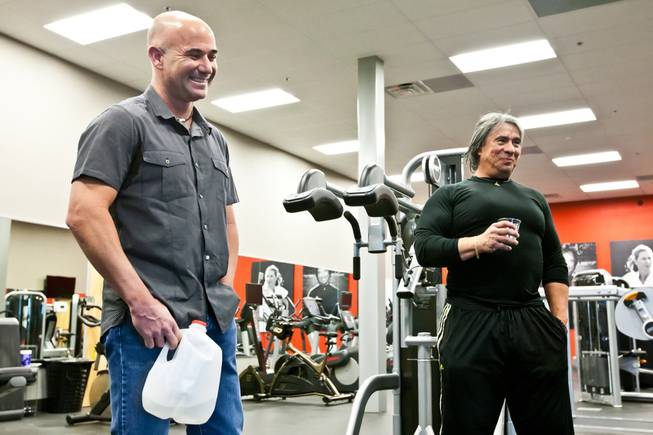 Tennis champion Andre Agassi and trainer Gil Reyes laugh together after demonstrating their award-winning BILT C.O.D. fitness machine, designed by Agassi and Reyes, in the gym of the BILT Headquarters in Las Vegas Friday, April 26, 2013.