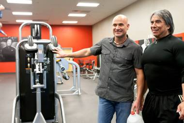 Tennis champion Andre Agassi and trainer Gil Reyes pose together for a Twitter photo after demonstrating their award-winning BILT C.O.D. fitness machine, designed by Agassi and Reyes, in the gym of the BILT Headquarters in Las Vegas Friday, April 26, 2013.