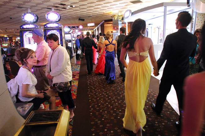 Gamblers watch as a group of Green Valley High School students walk through the Rio on their way to the Penn and Teller show on their prom night Saturday, April 27, 2013.