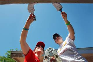 Laura Hoffmann, left, and Shawn Simon paint trim on a house as part of National Rebuilding Day Saturday, April 27, 2013.