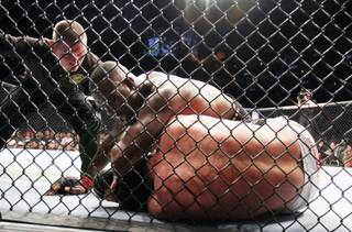 Champion Jon Jones, top, lands an elbow against Chael Sonnen during their UFC 159 light heavyweight title bout in Newark, N.J., Saturday, April 27, 2013. Jones retained his title via first-round TKO.