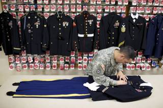 Staff Sgt. Miguel Deynes prepares the dress uniform of Capt. Aaron Blanchard, an Army pilot who was killed in Afghanistan, at the Dover Air Force Base in Deleware, April 27, 2013. At the Dover Port Mortuary, where the bodies of service members are brought to be prepared for funeral, no detail is too small, whether the coffin is closed or the body slated for cremation. (Ashley Gilbertson/The New York Times)