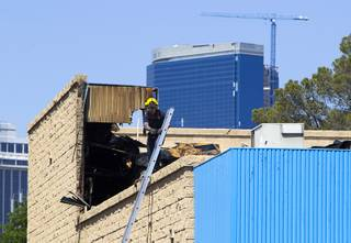 A firefighter prepares to descend a ladder after a fire at a medical building at Maryland Parkway near Vegas Valley Drive Wednesday,  May 1, 2013.