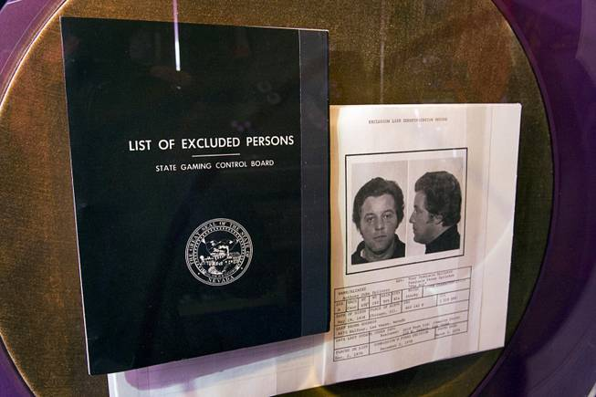 "A Black Book, a State Gaming Control Board list of people excluded from Nevada casinos, is displayed at the Mob Museum in downtown Las Vegas Monday, Feb. 13, 2012. At right is a page on former mobster Tony ""The Ant"" Spilotro, who was removed from the book only after his death."