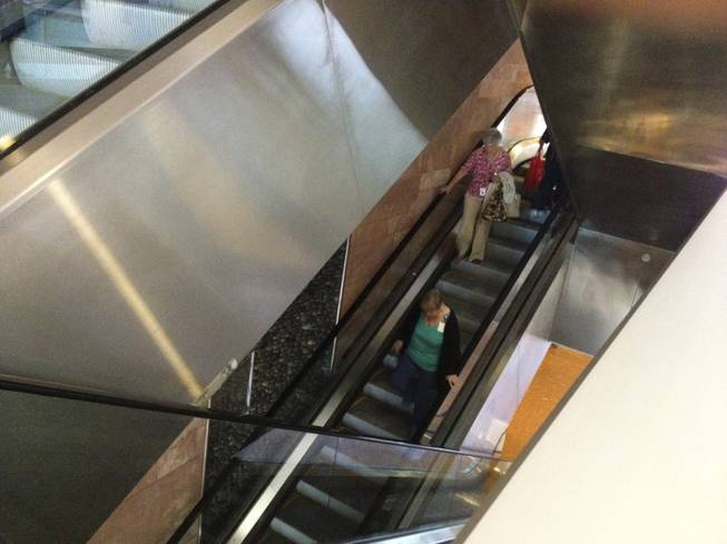 Two women are seen walking down the escalator at the Regional Justice Center due to an afternoon power outage Thursday, May 2, 2013.