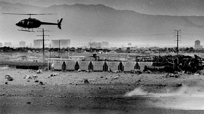 A helicopter flies over the smoldering remains of the Pacific Engineering Production Company of Nevada after two large explosions destroyed the plant, May 7, 1988.