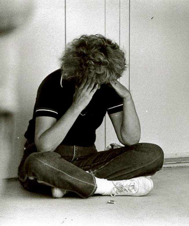 A worried parent cries at Cannon Junior High School on May 5, 1988, the day after blasts destroyed the Pacific Engineering Production Company of Nevada complex, killing two people and injuring 300.