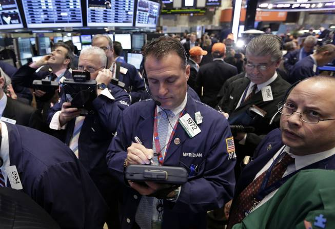 In this Thursday, May 2, 2013, photo, traders gather at a post on the floor of the New York Stock Exchange. Stock markets edged higher on Friday May 3, 2013, ahead of the release of the U.S. government's monthly unemployment report, a key measure of the health of the world's largest economy.
