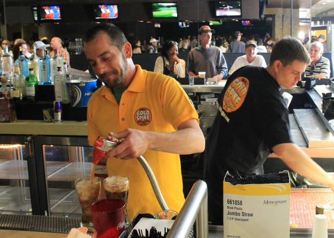 Bartender J.C. Kelley pours a couple of sodas about an hour before the doors closed for the final time April 14, 2013, at Gold Spike in Downtown Las Vegas. Gold Spike is reopening Monday, May 6, 2013, as a bar and restaurant.