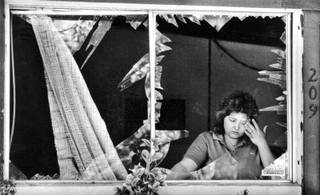 Barbara Hepworth assesses the damage to her home May 6, 1988. Windows and doors of homes and businesses nearby were shattered when two blasts destroyed the Pacific Engineering Production Company of Nevada plant May 4, 1988.