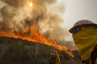 A firefighter watches a wildfire along a hillside in Point Mugu , Calif. Friday, May 3, 2013. Firefighters got a break as gusty winds turned into breezes, but temperatures remained high and humidity levels are expected to soar as cool air moved in from the ocean and the Santa Ana winds retreated.