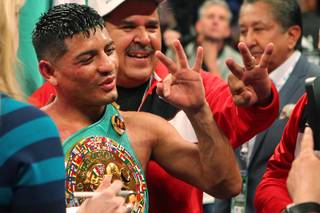 Abner Mares holds up three fingers signifying championships in three different weight classes after defeating featherweight champion Daniel