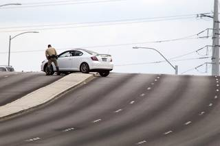 A Metro Police officer looks over a vehicle after an accident between a car and a Metro Police motorcycle officer on the Durango Drive overpass over the Summerlin Parkway Wednesday, May 8, 2013.