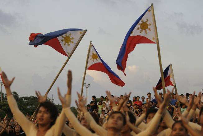 Filipinos watch as dancers use Philippine flags as part of their performance during the 113th Philippine Independence Day celebrations at  Manila's Rizal Park, Philippines on Sunday June 12, 2011. Philippine independence from Spain was proclaimed on June 12, 1898.