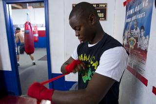 Mike McCallum Jr., a Silverado High School student, wraps his hands before a workout with his father at Johnny Tocco's Boxing Gym Thursday, May 9, 2013.  Mike McCallum Sr., known as the