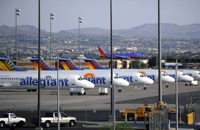 In this Thursday, May 9, 2013, photo, a Southwest airliner comes in for a landing as a row of Allegiant Air jets are parked at McCarran International Airport in Las Vegas.