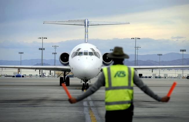 In this Thursday, May 9, 2013, photo, an airline ground worker guides an incoming Allegiant Air jetliner at McCarran International Airport, in Las Vegas. While other U.S. airlines have struggled with the ups and downs of the economy and oil prices, tiny Allegiant Air has been profitable for 10 straight years.