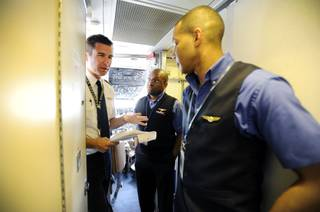 In this Thursday, May 9, 2013, photo, an Allegiant Air Capt. Bret Whalen, left, discusses the flight plan with flight attendants Antron Johnson, center, and John Taylor before their flight to Laredo, Tex, at McCarran International Airport in Las Vegas. While other U.S. airlines have struggled with the ups and downs of the economy and oil prices, tiny Allegiant Air has been profitable for 10 straight years.