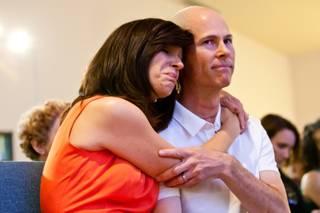 Karen Turnbull embraces her husband, Mike Turnbull, a trombonist who is recovering from stage-four thyroid cancer, during a musical fundraiser to help them with medical bills held at New Song Anthem Church Saturday, May 12, 2013.