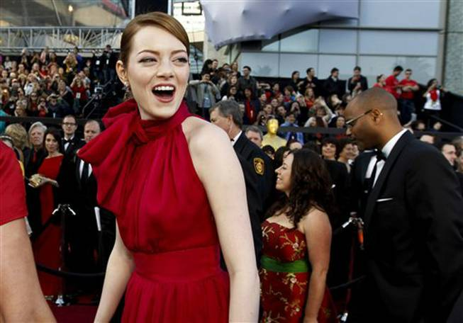 Emma Stone arrives before the 84th Academy Awards on Sunday, Feb. 26, 2012, in Los Angeles. (AP Photo/Chris Carlson)