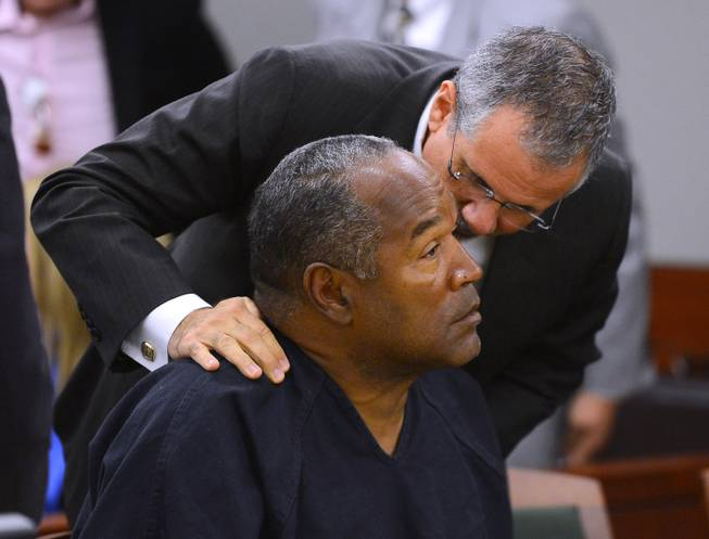 O.J. Simpson and his defense attorney Ozzie Fumo confer during an evidentiary hearing for Simpson in Clark County District Court on May 17, 2013, in Las Vegas.