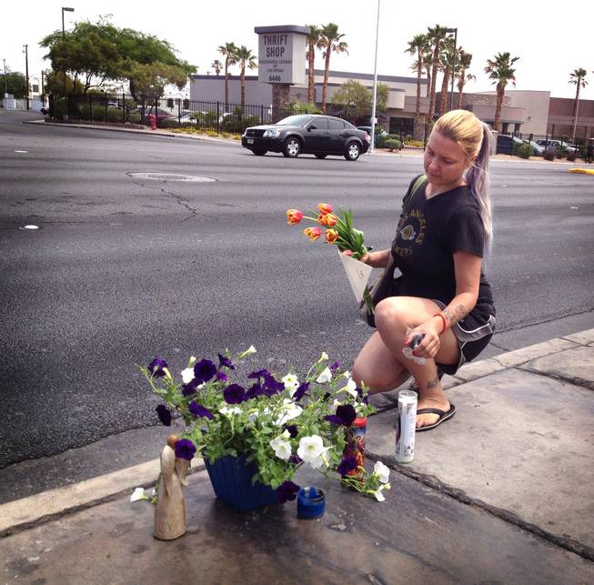 Renee Gardner, 38, adds a bouquet of flowers, card and candle to a memorial for 15-year-old Marcos Vincente Arenas on Friday, May 17, 2013. Metro Police say Arenas, a freshman at Bonanza High School, was run over the previous day as he was being robbed of his iPad. Arenas was transported to University Medical Center, where he died of his injuries.