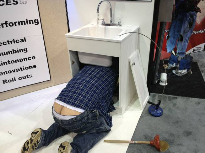 "A ""plumber"" fixes a sink at Ideal Services' booth at RECon, the retail industry trade show at the Las Vegas Convention Center, on May 20, 2013. The mannequin was used to demonstrate one of many problems that could result from hiring the wrong repairman."