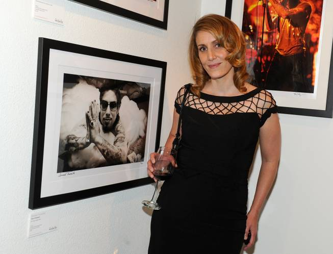 Denise Truscello, with her 2004 photograph of Dave Navarro, at the grand opening of Rock Paper Photo Gallery at The Hard Rock Hotel on Saturday, May 18, 2013.