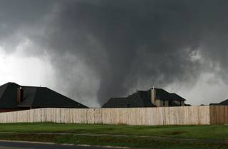 A tornado moves past homes in Moore, Okla. on Monday, May 20, 2013.