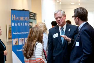 Chief Executive Officer Brian Brannman, of University Medical Center, visits with .Lisa Levine, left, and Charles Blumenthal, right, during the networking reception held prior to the paneled discussions on downtown medical developments hosted by the Southern Nevada Medical Industry Coalition at the Historic 5th Street School Wednesday, May 22, 2013.