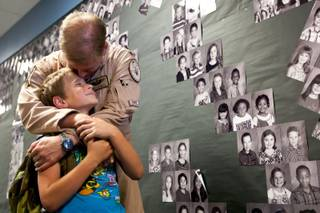 Aaron Powell, 9, receives a kiss from his dad in the school hallway after he surprised him by coming home early from serving in Afghanistan at Henry and Evelyn Bozarth Elementary School Thursday, May 23, 2013.