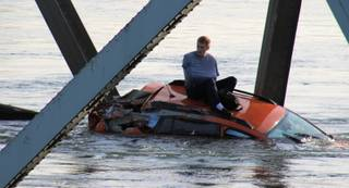 In this photo provided by Francisco Rodriguez, a man is seen sitting atop a car that fell into the Skagit River after the collapse of the Interstate 5 bridge there minutes earlier Thursday, May 23, 2013, in Mount Vernon, Wash.