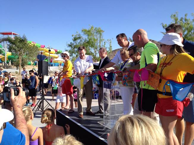 Tennis legend Andre Agassi, Clark County Commissioner Susan Brager and Wet 'n' Wild Las Vegas investors Roger and Scott Bulloch of SPB Partners prepare to cut a ceremonial red ribbon made fittingly of swimwear during the park's grand opening on Friday, May 24, 2013. Kids in candy-colored swimsuits squirmed anxiously during the ceremony as they waited for the green light to ride the slides.