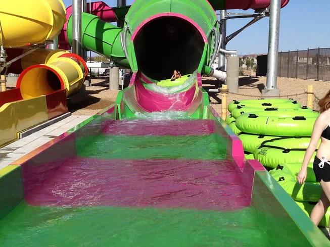 Kids tube down one of the Wet n Wild large slides during the park's grand opening on Friday, May 24, 2013. The 41-acre water park on Fort Apache Road near the 215 Beltway was opened to visitors for the first time.