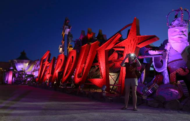 A tourist takes a photo at the Neon Museum in Las Vegas on Friday, May 24, 2013. For the past six months, visitors have had to squint up at the hulking metal forms through the desert sun. On Friday, the museum unveiled nighttime hours.