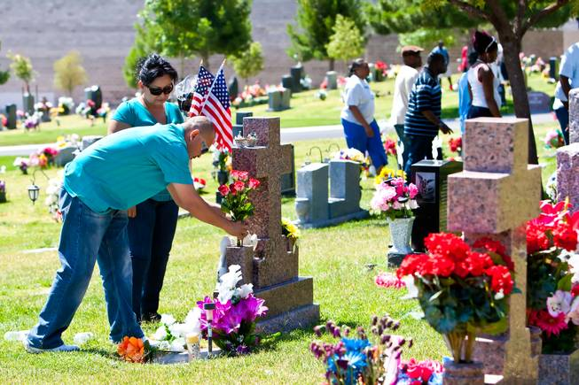 Following the 48th Annual Memorial Day Service, Trini and Paula Torres place flowers and American flags on a grave of their loved one at the Palm Downtown Mortuary and Cemetery in Las Vegas, Monday, May 27, 2013.