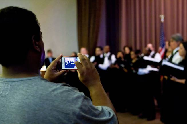 A guest shoots a video of the Las Vegas Master Singers Chamber Chorale perform during the 48th Annual Memorial Day Service at the Palm Downtown Mortuary and Cemetery in Las Vegas, Monday, May 27, 2013.