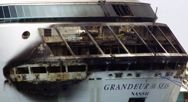 The fire-damaged exterior of Royal Caribbean's Grandeur of the Seas cruise ship is seen while docked in Freeport, Grand Bahama island, Monday, May 27, 2013. Royal Caribbean said the fire occurred early Monday while on route from Baltimore to the Bahamas on the mooring area of deck 3 and was quickly extinguished. All 2,224 guests and 796 crew were safe and accounted for.
