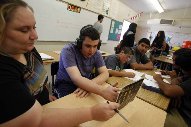 Ido Kedar, second from left, who is a non-verbal autistic teenager, answers a question with the use of a letter board held by behavior intervention implementer Anna Page during a class at Canoga Park High School in Canoga Park, Calif., in June 2013. Kedar wears headphones due to his heightened sensitivity to sound.