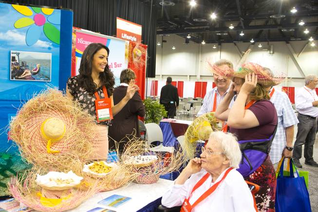 Farah Eslaquit, 2012 Miss Nicaragua, hands out straw hats at the Nicaragua Tourism Board booth during the 2013 AARP Convention on Thursday, May 30, 2013.