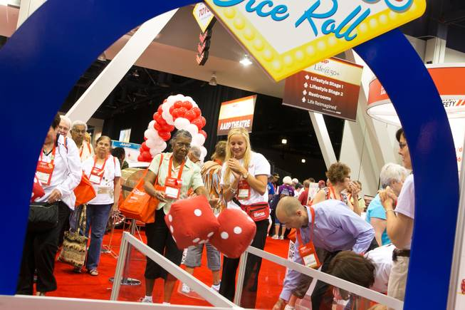 Betty Gibson of Chicago rolls a pair of oversized dice at the AARP Driver Safety booth during the 2013 AARP Convention on Thursday, May 30, 2013.
