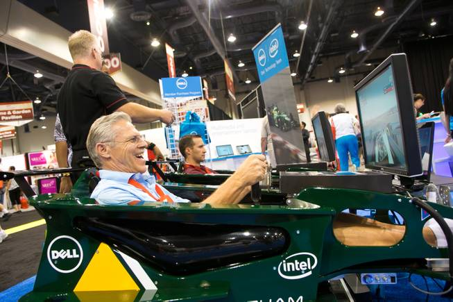 Bob Scheuerell of Buckeye, Ariz., smiles as he drives a Formula One simulator at the Dell computers booth during the 2013 AARP Convention on Thursday, May 30, 2013.
