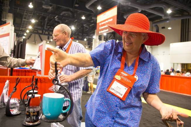 "Barbara West of Boulder City demonstrates a ""SpillNot"" cup caddy she just purchased at the 2013 AARP Convention on Thursday, May 30, 2013."