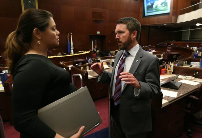 Nevada Assembly Democrats Teresa Benitez-Thompson and David Bobzien talk on the Assembly floor at the Legislative Building in Carson City, Nev., on Wednesday, April 10, 2013. Benitez-Thompson's Government Affairs committee approved Bobzien's bill to bar Pershing County from imposing regulations and fees on Burning Man.