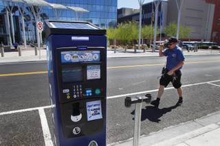 City of Las Vegas parking meter technician Matt Lancaster walks past one of the city's new electronic, solar powered parking meters while removing old meters Tuesday, June 4, 2013.